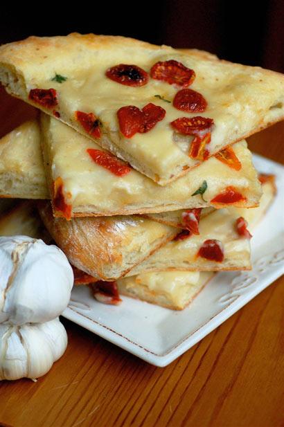 Pizza con ajos asados, crema de coco y tomates secos