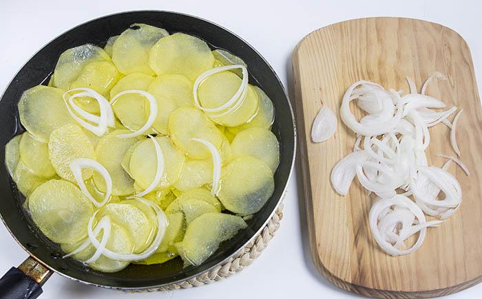 Añadiendo cebolla a las patatas