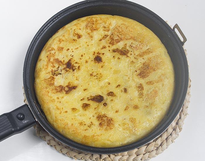 Tortilla de patatas con cebolla cocinándose